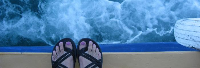 Womans feet in sandles on the edge of a ferry boat with frothy foam traveling over the water